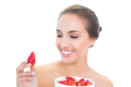 Young brunette woman smiling at a strawberry on white  photo