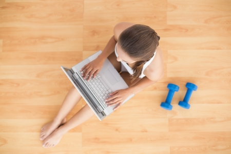 Sporty brunette using a laptop and sitting next to dumbbells on the floor photo