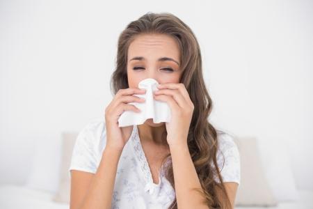 Attractive brunette blowing her nose in bright bedroom photo