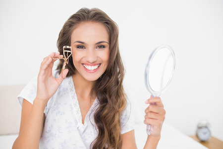Smiling attractive brunette holding an eyelash curler and mirror in bright bedroom photo