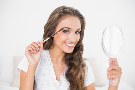 Smiling attractive brunette using eyebrow brush and mirror in bright bedroom photo