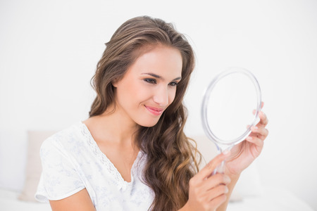 Grinning attractive brunette looking at mirror in bright bedroom Stock Photo