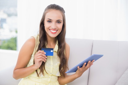 Smiling young brunette holding credit card and tablet in bright living room photo