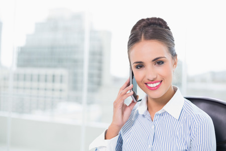 Cheerful brunette businesswoman phoning with smartphone in bright office photo