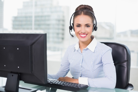 Cheerful brunette businesswoman using headset in bright office photo