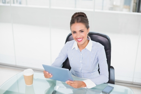 Cheerful brunette businesswoman holding tablet in bright office photo