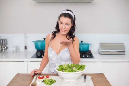 Peaceful pretty brunette preparing healthy salad blowing kiss in bright kitchen photo