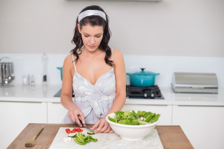 Pretty brunette chopping vegetables in bright kitchen photo