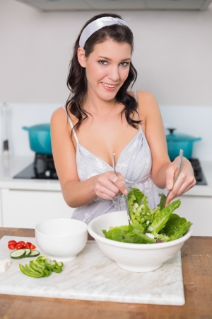Cheerful pretty brunette mixing healthy salad in bright kitchen photo