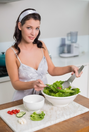 Smiling cute brunette mixing healthy salad in bright kitchen photo