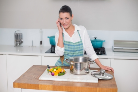 Smiling gorgeous woman wearing apron having a call in bright kitchen photo