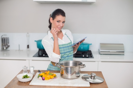 Happy gorgeous woman wearing apron using tablet while cooking in bright kitchen photo