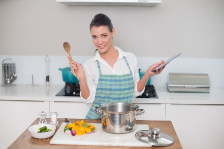 Smiling gorgeous woman wearing apron using tablet while cooking in bright kitchen photo