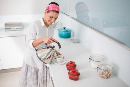 Smiling gorgeous woman preparing tea in bright kitchen photo