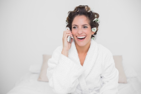 Laughing natural brunette phoning and sitting on bed photo