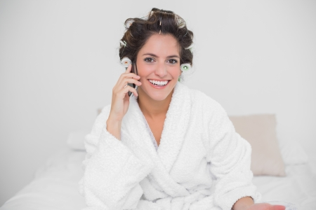 Smiling natural brunette phoning and sitting on bed photo