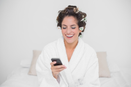 Laughing natural brunette looking at smartphone in bedroom photo