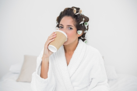 Calm natural brunette drinking from disposable cup in bedroom photo