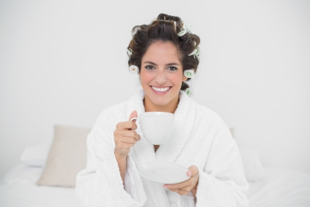 Smiling natural brunette holding a mug in bedroom photo