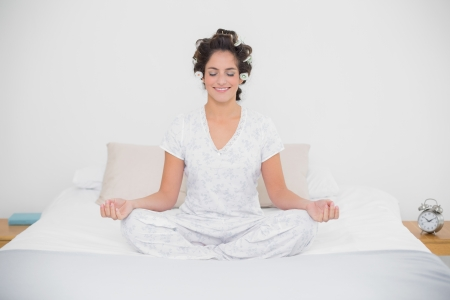 Smiling natural brunette sitting in lotus pose in bedroom photo