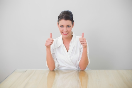 Smiling brown haired businesswoman giving thumbs up to camera in bright office photo