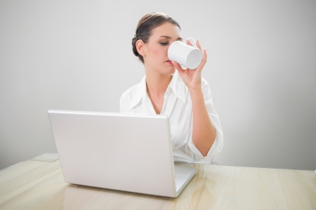 Serious businesswoman working on laptop drinking coffee in bright office Stock Photo - 25431969