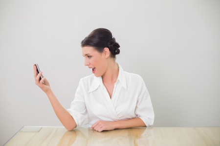 Surprised brown haired businesswoman text messaging in bright office photo