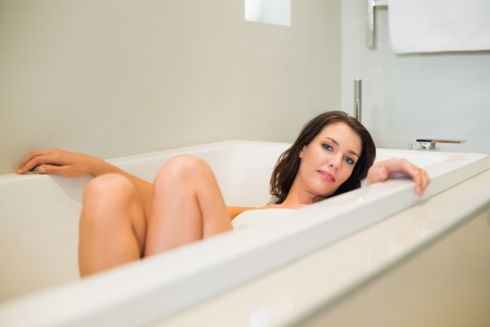 Attractive natural brown haired woman relaxing in the bathtub in a bright bathroom photo