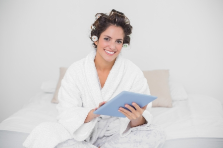 Smiling natural brunette using tablet in bedroom photo