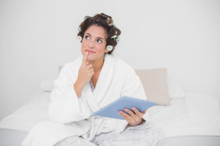 Thoughtful natural brunette holding tablet in bedroom photo