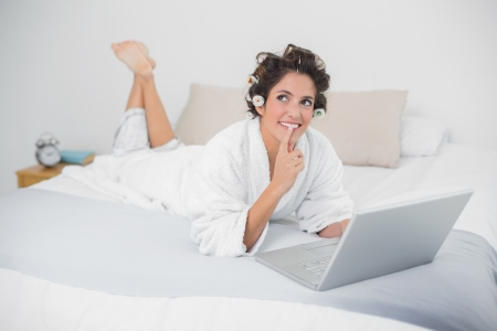 Pensive natural brunette using laptop in bedroom photo