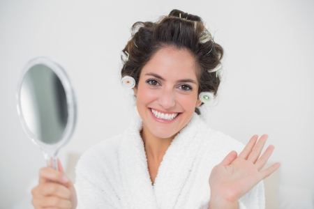 Cheerful natural brunette holding mirror and waving in bedroom photo