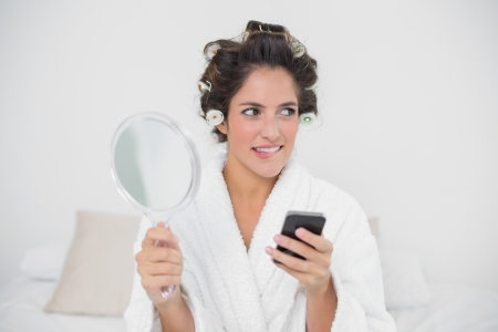 Pensive natural brunette holding mirror and smartphone in bedroom photo