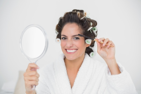 Smiling natural brunette using eyebrow brush in bedroom photo