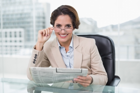 Smiling businesswoman holding newspaper at her desk in bright office photo