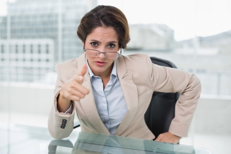 Irritated businesswoman looking at camera in bright office photo