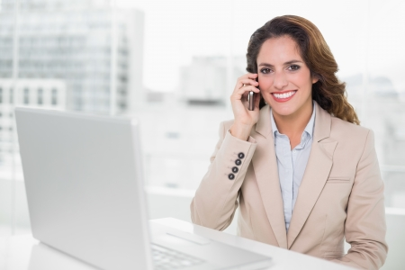 Happy businesswoman on the phone at her desk in bright office photo
