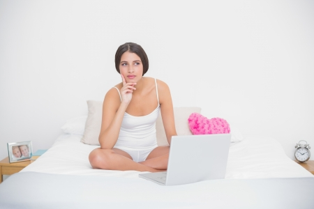 Thinking young brown haired model in white pajamas using a laptop in bright bedroom photo