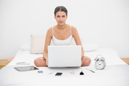 Irritated young brown haired model in white pajamas holding a laptop in bright bedroom photo