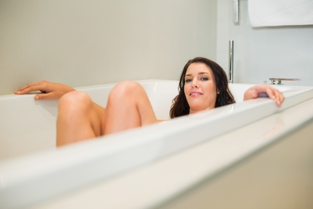 Smiling natural brown haired woman relaxing in a bathtub in a bright bathroom photo