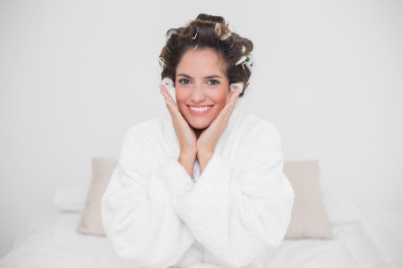 Cheerful natural brunette looking at camera and sitting on bed photo