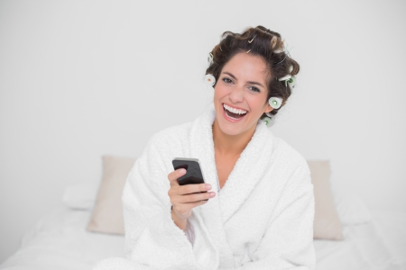 Laughing natural brunette holding smartphone in bedroom photo