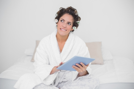 Pensive natural brunette holding tablet in bedroom photo