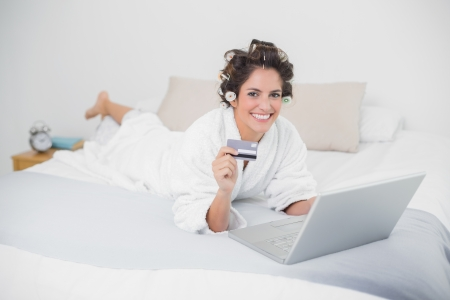 Smiling natural brunette using credit card and laptop in bedroom photo