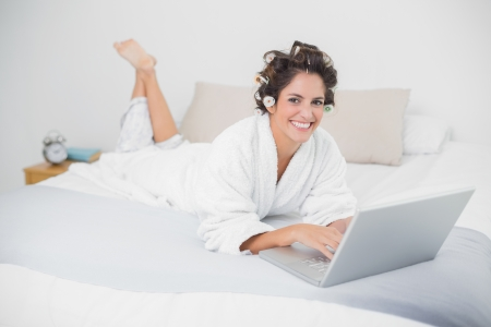 Smiling natural brunette using laptop in bedroom photo