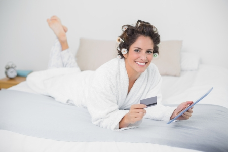Smiling natural brunette using tablet and credit card in bedroom photo