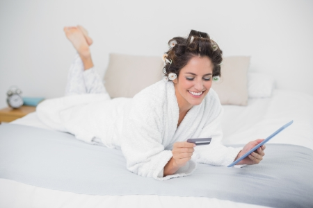 Happy natural brunette using tablet and credit card in bedroom photo