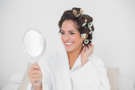 Cheerful natural brunette loking at mirror in bedroom photo