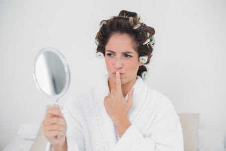 Pensive natural brunette looking at mirror in bedroom photo