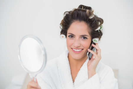 Smiling natural brunette using phone in bedroom photo